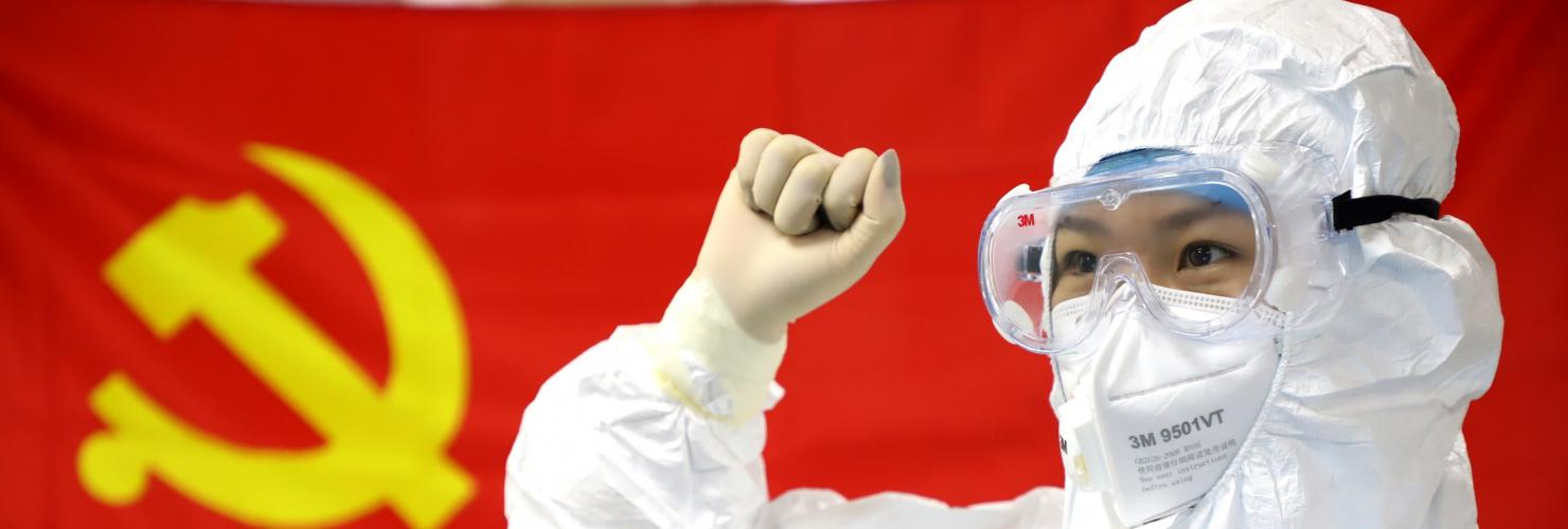 Chinese medical worker in front of a flag of the CCP