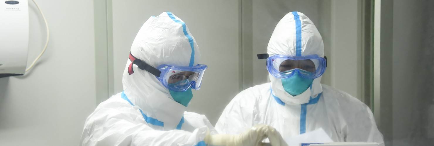 Cao Ting (L) and her colleague prepare to work in the laboratory of Xiaogan's center for disease control and prevention in central China's Hubei Province.