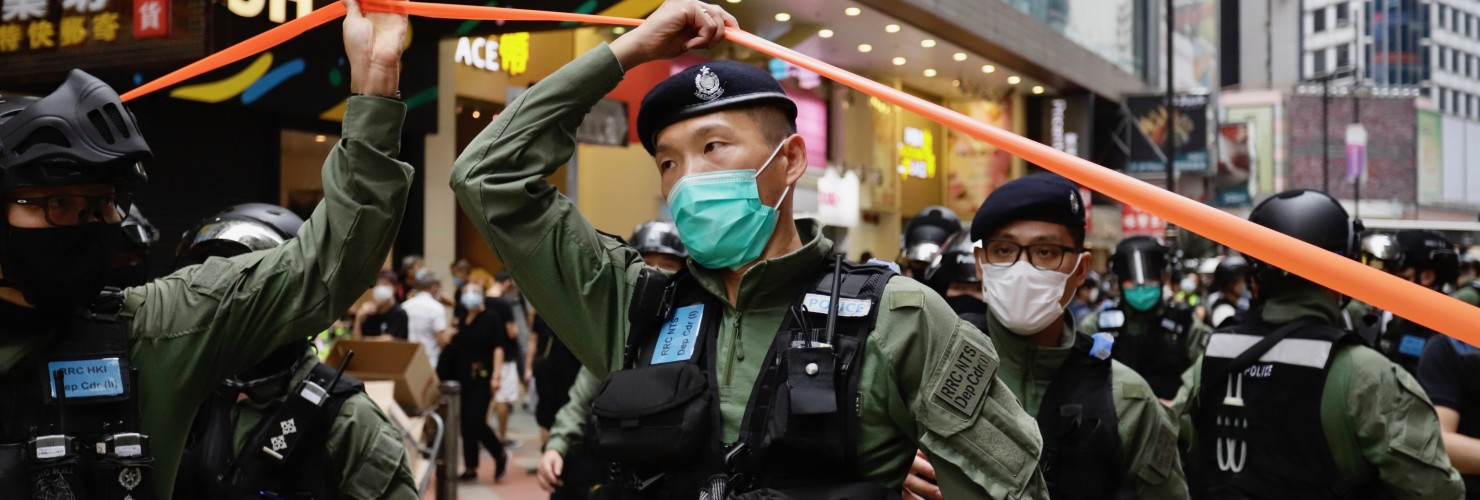 Policeman pass through a cordon line in the city centre on the PRC national day in Hong Kong.