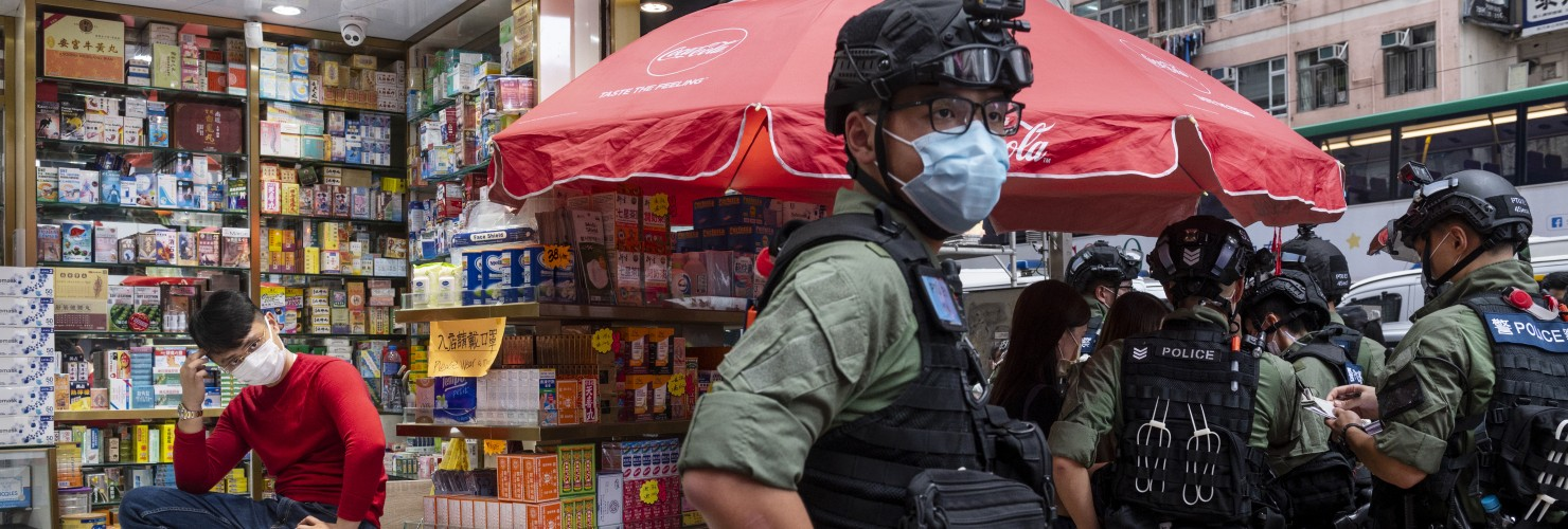 A pharmacy sales person sits on a chair as riot police officers stop and search people on the vicinity during a banned protest in Hong Kong, China, on October 1, 2020.