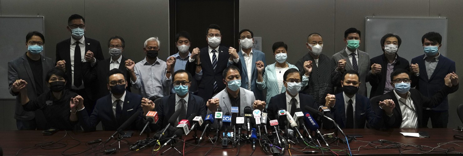 Hong Kong's pro-democracy legislators pose for a photo before a press conference at the Legislative Council in Hong Kong, Wednesday, Nov. 11, 2020.