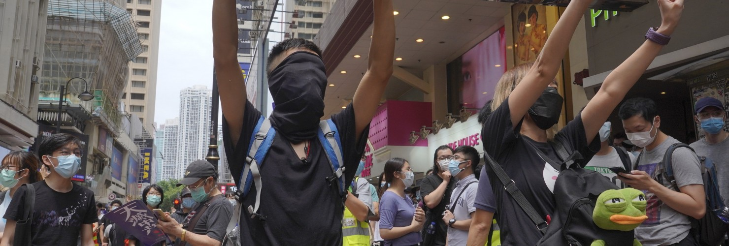 "Protesters gesture with five fingers, signifying the ""Five demands - not one less"" as they march along a downtown street during a pro-democracy protest against Beijing's national security legislation in Hong Kong, Sunday, May 24, 2020. picture alliance / AP Photo"