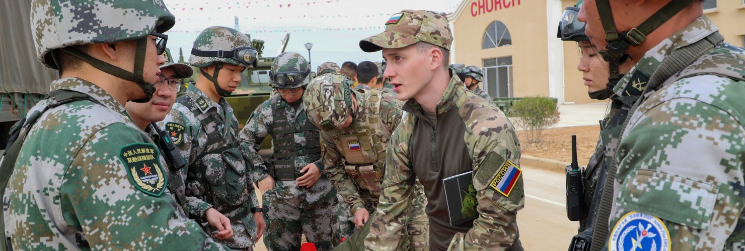 Chinese and Russian soldiers communicate with each other during a joint exercise