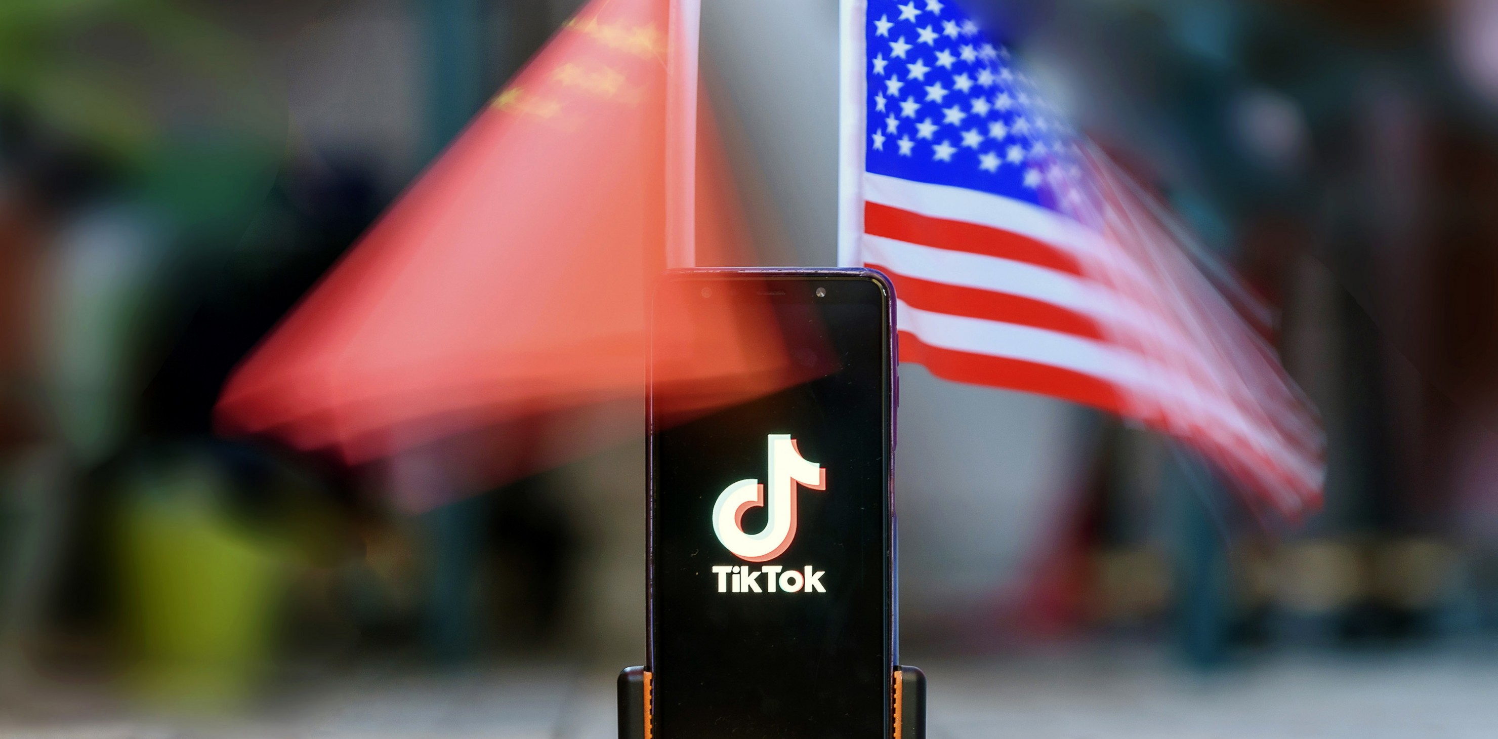 Smartphone showing the Logo of TikTok in front of US and Chinese flags