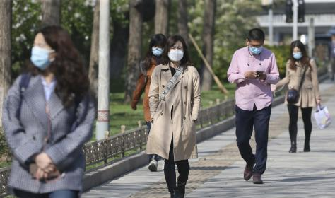 People wearing facemasks at a street in Beijing