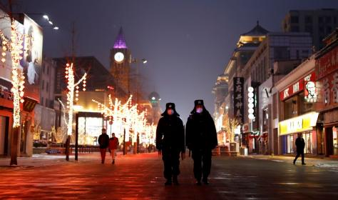 Security guards walking down Wangfujing street in Beijing.