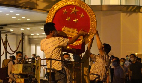 Workers place a national emblem outside the Metropark Hotel Causeway Bay