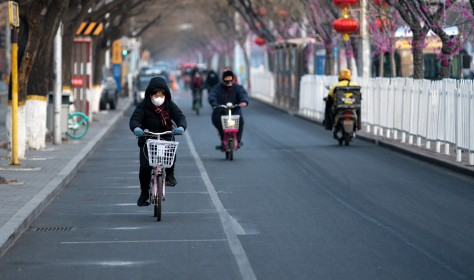 People riding bicycles in a street in Beijing.