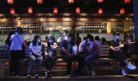People, most with masks, enjoy visiting an event featuring old streets and atmosphere in Beijing, China.