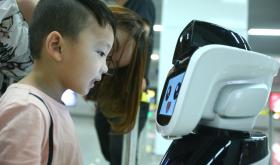 "A boy looks at the intelligent robot ""Xiaogui"" at Yinghua Park metro station in Ningbo, Zhejiang Province."