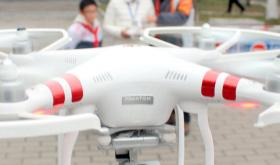 A Chinese girl operates an unmanned aerial vehicle (UAV), or drone, in Suzhou city, east China's Jiangsu province