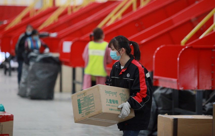 Workers sort packages at the transfer site of a Courier company in Guangling District, Yangzhou City